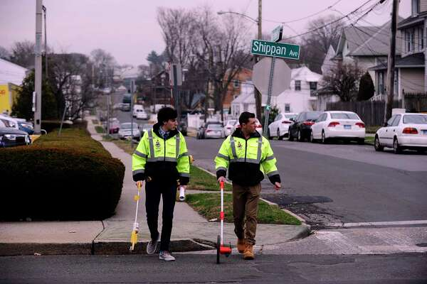 Luke Buttenwieser, an intern with the Transportation, Traffic and Parking Department, assists Traffic Engineer Garrett Bolella with surveying and marking new crosswalk and traffic patterns at Shippan and Wardell Avenues in Stamford, Conn. on March 20, 2020.