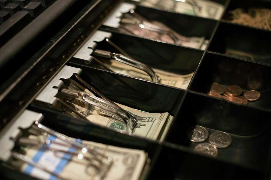 This Dec. 25, 2018, photo shows twenty dollar bills in a register at a business in Eagle, Colo. While many business owners know they'll owe the government less money or perhaps get refunds under the new tax law, others are still unsure about what they might have to pay while they file their returns. They need to be sure they have some extra cash, or access to financing, in case they're facing sizeable tax bills.(AP Photo/Jenny Kane) Photo: Jenny Kane, STF / Associated Press / AP