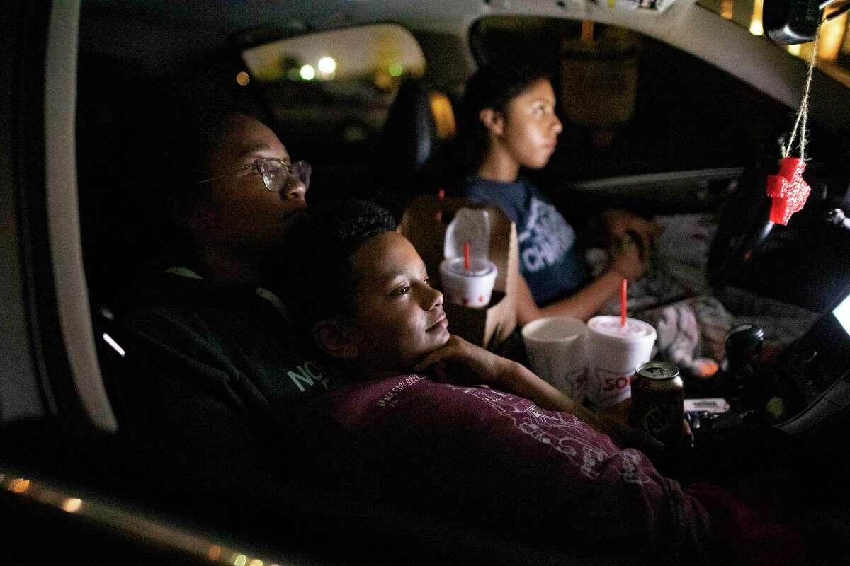 """Lazarus Brown rests with his sister, Alana, left, and Malia Bennett, right, as they watch a projected movie at the EVO Entertainment facility in Schertz on Friday night, March 27, 2020. The EVO Drive-In showed """"Spider-Man Homecoming,"""" free of charge, although patrons were encouraged to buy food and beverage to support employees working the show. The event provided a chance for people to see a movie while maintaining social distancing to combat the spread of the coronavirus."""