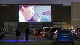 "Cars are lined up at the EVO Entertainment facility in Schertz as their occupants watch a movie projected on a wall on Friday night, March 27, 2020. The EVO Drive-In showed ""Spider-Man Homecoming,"" free of charge, although patrons were encouraged to buy food and beverage to support employees working the show. The event provided a chance for people to see a movie while maintaining social distancing to combat the spread of the coronavirus."
