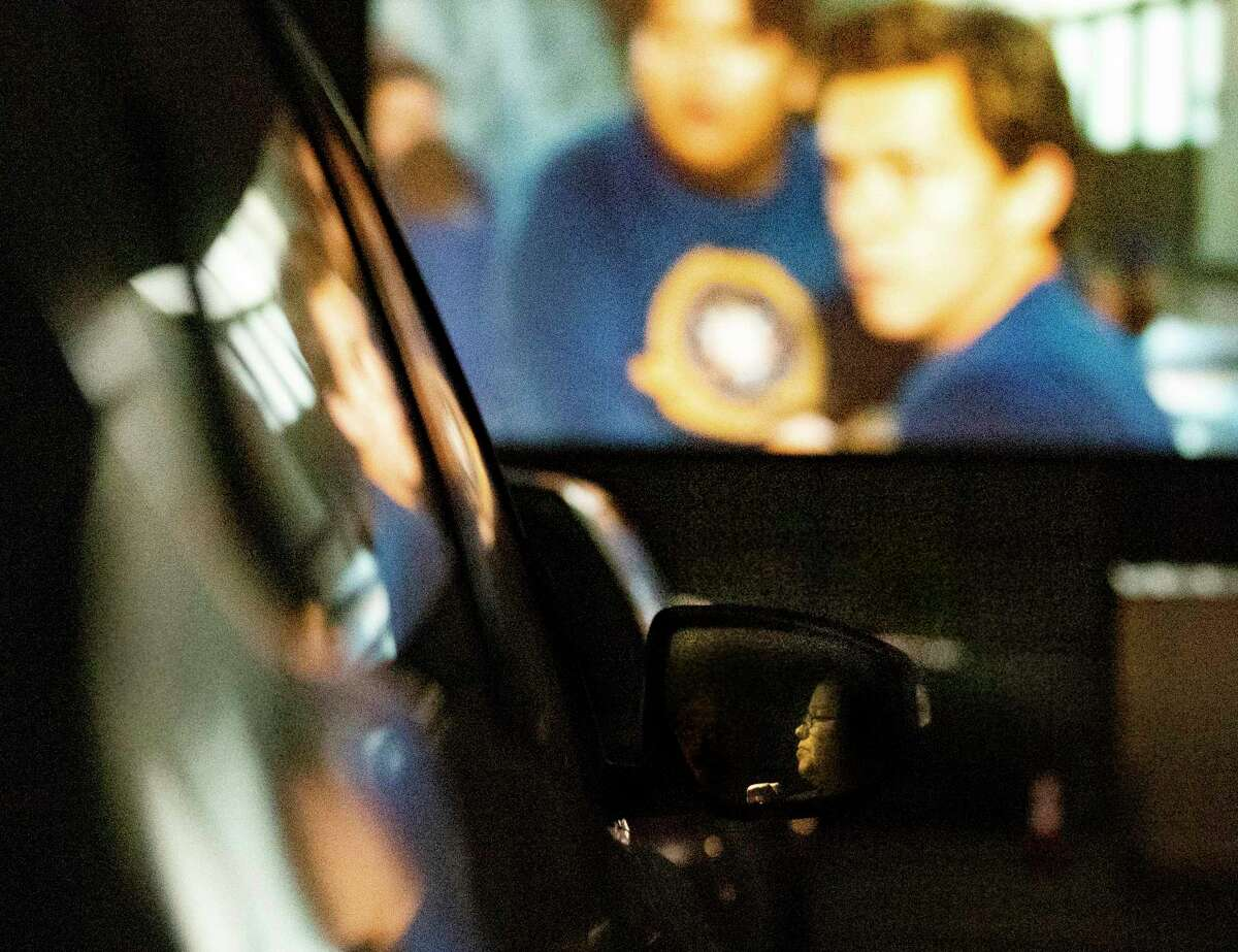 """Kim Taylor is reflected in a rear-view mirror while watching a movie projected outdoors at the EVO Entertainment facility in Schertz on Friday night, March 27, 2020. The EVO Drive-In showed """"Spider-Man Homecoming,"""" free of charge, although patrons were encouraged to buy food and beverage to support employees working the show. The event provided a chance for people to see a movie while maintaining social distancing to combat the spread of the coronavirus."""