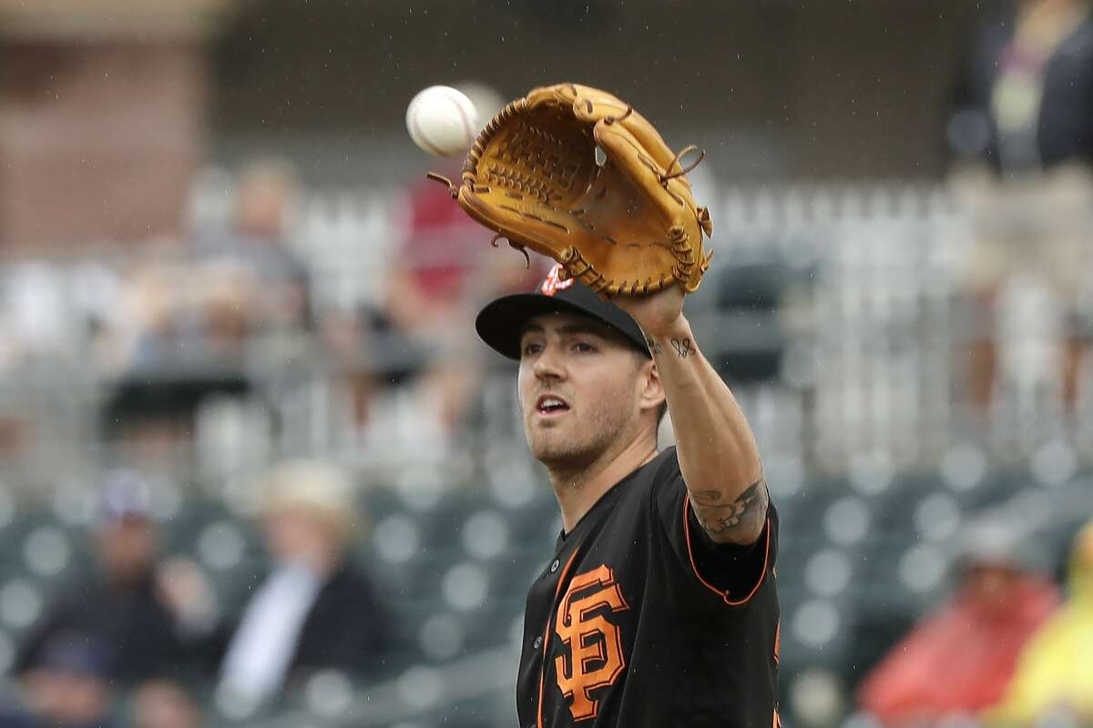 San Francisco Giants starting pitcher Kevin Gausman reaches for the ball against the Texas Rangers during a spring training baseball game Wednesday, March 11, 2020, in Surprise, Ariz. (AP Photo/Elaine Thompson)