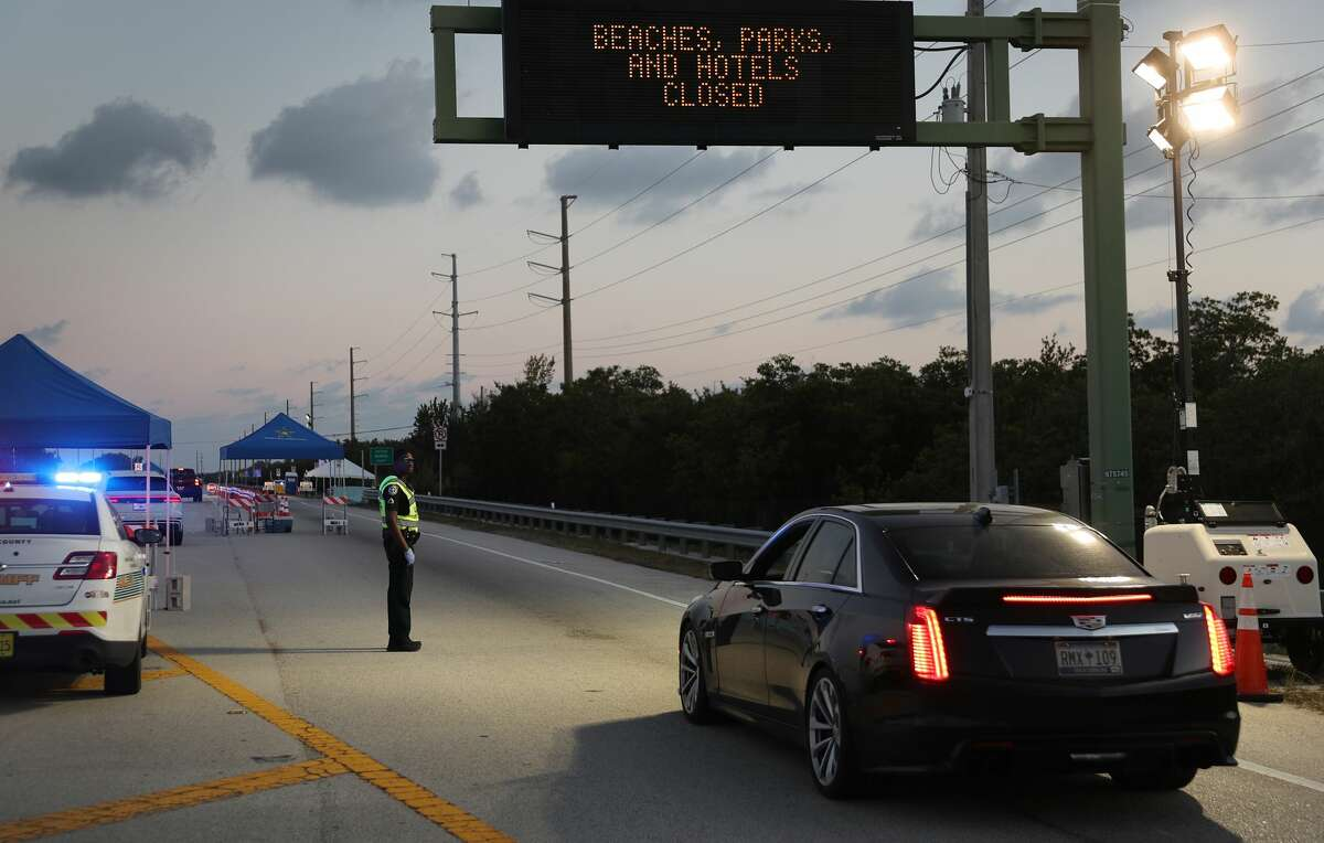 Monroe County Sheriff deputy Jamie Miller mans a checkpoint on U.S. 1 leading into the Florida Keys on March 27, 2020 in Florida City, Florida. Monroe County administrators made the decision to prohibit tourists and only allow property owners and people who show they legitimately work in the Keys to pass through the roadblocks in an effort to stop the spread of COVID-19. (Photo by Joe Raedle/Getty Images)