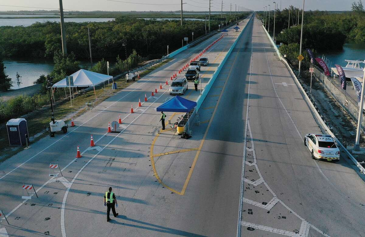 An aerial view from a drone shows Monroe County Sheriff deputies as they man a checkpoint on U.S. 1 leading into the Florida Keys on March 27, 2020 in Florida City, Florida. Monroe County administrators made the decision to prohibit tourists and only allow property owners and people who show they legitimately work in the Keys to pass through the roadblocks in an effort to stop the spread of COVID-19. (Photo by Joe Raedle/Getty Images)