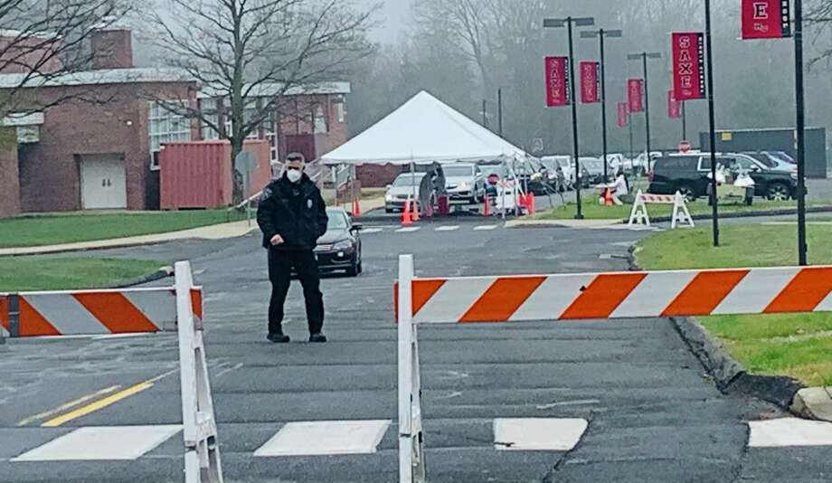 A New Canaan police officer wears a protective mask while monitoring a coronavirus testing site. Photo: John Kovach / Hearst Connecticut Media / New Canaan Advertiser