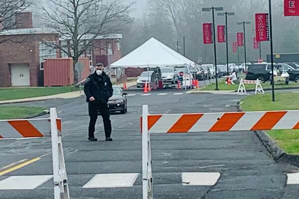 A New Canaan police officer wears a protective mask while monitoring a coronavirus testing site.