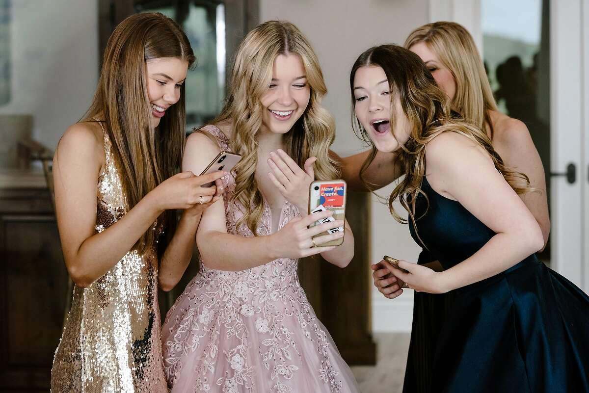 From left Allison Reese, Natalie Reese, Brooke Reese, and their mother Laurie Reese, watch TikTok videos of themselves celebrating the girls' canceled prom from their home in Danville, Calif, on Saturday, March 28, 2020.