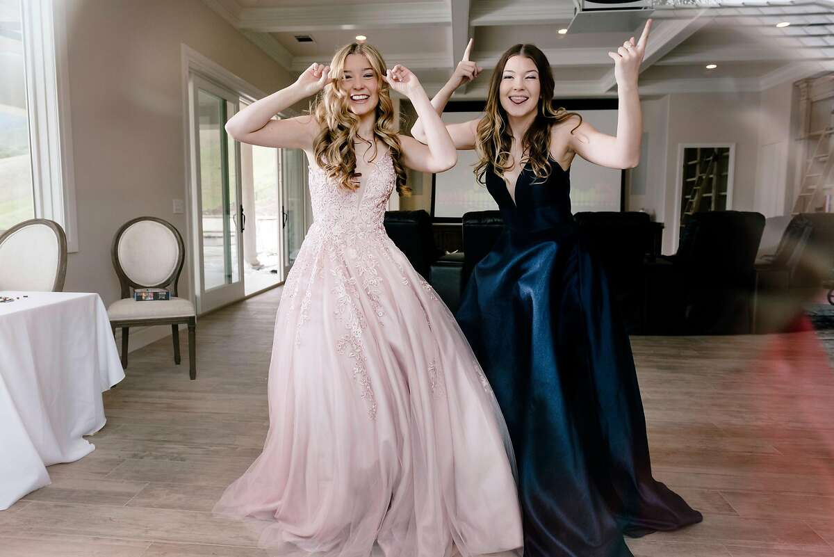 Natalie Reese, left, and her twin sister Brooke Reese film TikTok videos of themselves celebrating their canceled prom from their home in Danville, Calif, on Saturday, March 28, 2020.