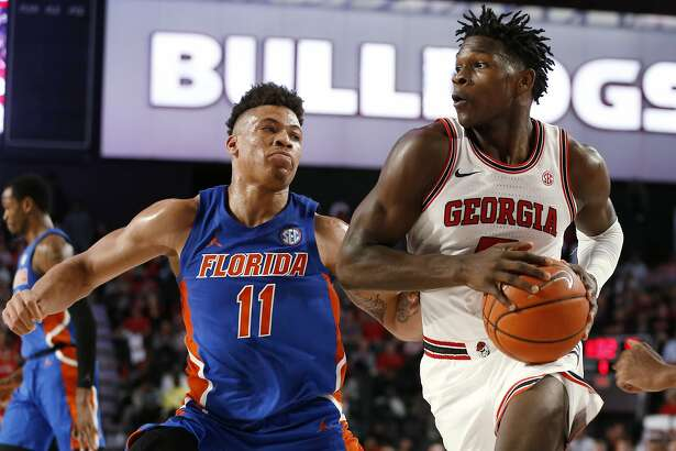 Georgia's Anthony Edwards (5) moves the ball pasy Florida forward Keyontae Johnson (11) during the first half of an NCAA college basketball game Wednesday, March 4, 2020, in Athens, Ga. (Joshua L. Jones/Athens Banner-Herald via AP)