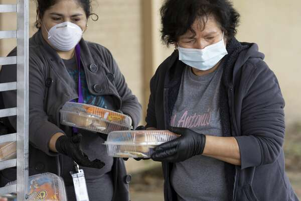 Alma Suarez (left) and Maria Martinez unloads a cart full of boxed lunches at CC Hardy Elementary in Willis, Tuesday, March 23, 2020. Willis ISD started distribution of Child Nutrition Meals which includes bagged breakfast and lunch in response to school closures throughout the county.