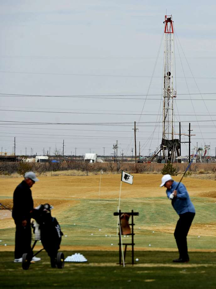 Golfers tee off on the driving range toward an active oil and gas location Feb. 13, 2019, at Midland Country Club. James Durbin / Reporter-Telegram Photo: James Durbin/Reporter-Telegram / © 2019 All Rights Reserved