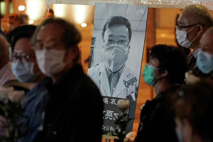 """FILE - In this Feb. 7, 2020, file photo, people wearing masks attend a vigil for Chinese doctor Li Wenliang, who was reprimanded for warning about the outbreak of the new coronavirus, in Hong Kong. China has taken the highly unusual move of exonerating the doctor who was reprimanded for warning about the coronavirus outbreak and later died of the disease. An official media report said police in Wuhan had revoked its admonishment of Dr. Li that had included a threat of arrest and issued a """"solemn apology"""" to his family. (AP Photo/Kin Cheung, File)"""