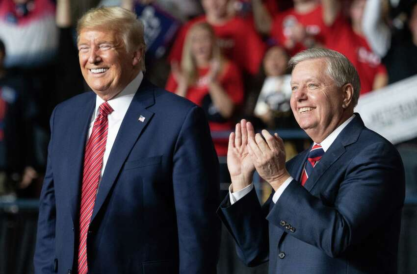 US president Donald Trump (L) smiles as he stands alongside US Senator Lindsey Graham (R), Republican of South Carolina, during a Keep America Great campaign rally for US President Donald Trump at the North Charleston Coliseum in North Charleston, South Carolina, February 28, 2020. (Photo by SAUL LOEB / AFP) (Photo by SAUL LOEB/AFP via Getty Images)