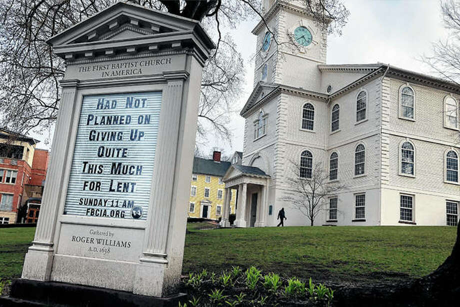 A man walks past First Baptist Church in America in Providence, Rhode Island. Americans are turning to humor in many forms, like the sign in front of the church, as they cope with the fear and anxiety the coronavirus pandemic has unleashed. Photo: William J. Kole | Associated Press