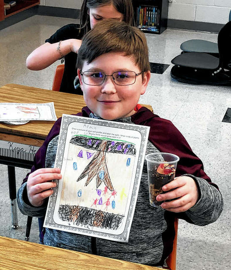 The Pike-Scott Agriculture in the Classroom program recently visited third-graders at Bluffs Elementary School to teach them about soil. Ryan Anders displays his soil profile drawing and edible soil profile treat, which included M&Ms (bedrock), chocolate chip cookies (subsoil) and Oreo cookies (topsoil).