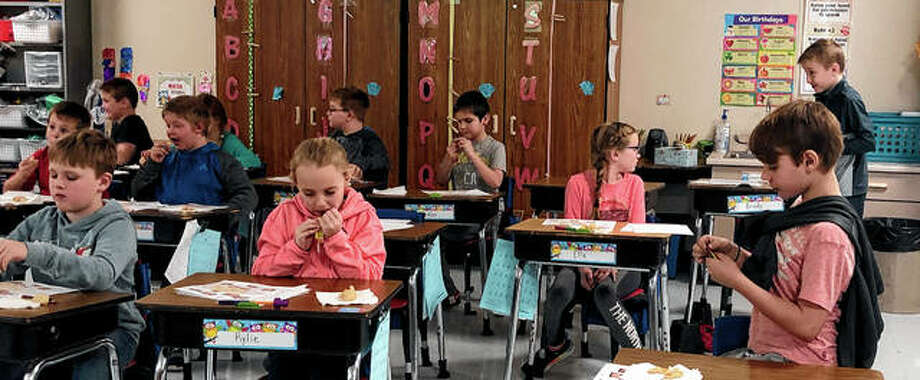 The Pike-Scott Agriculture in the Classroom program recently visited Pikeland Elementary School to share a lesson on pigs with third-graders. Mrs. Havens' students enjoy a pork-based snack — an Original Slim Jim — during the lesson.