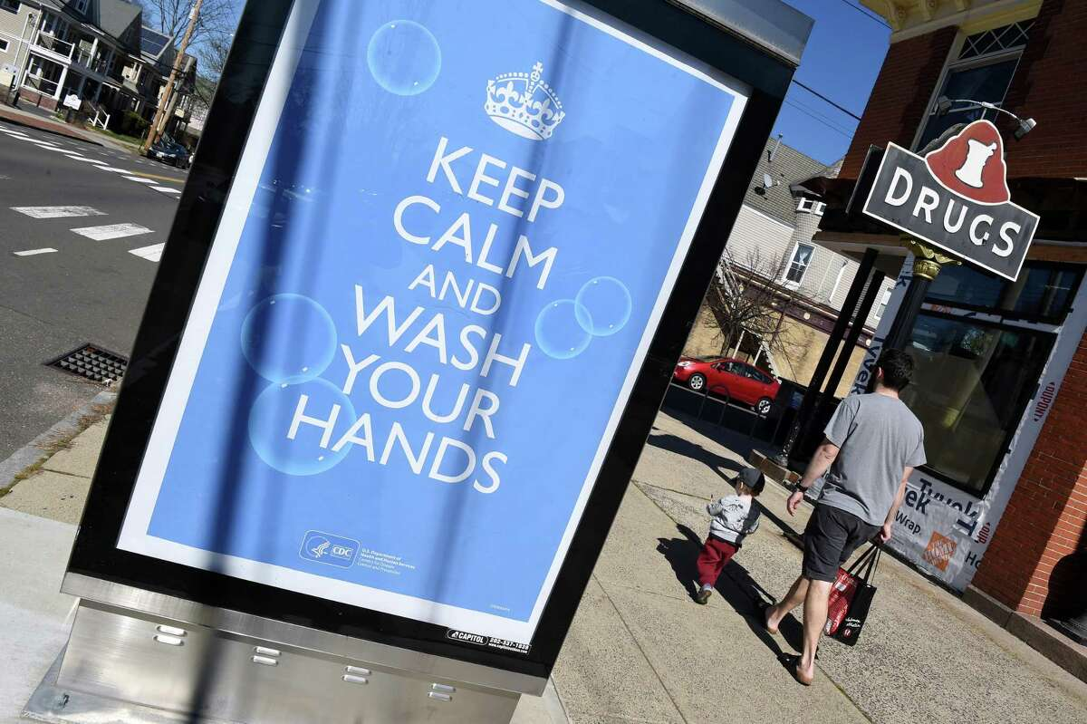 Leslie Robbins walks with his son past a Center for Disease Control and Prevention sign on Orange Street in New Haven stressing hand washing on March 27, 2020.