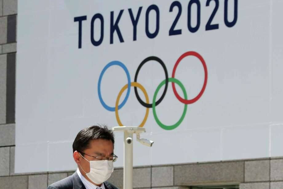 FILE - In this Wednesday, March 25, 2020, file photo, a man walks in front of a Tokyo Olympics logo at the Tokyo metropolitan government headquarters. The postponement of the Tokyo Games has catapulted the sports organizations that make up the backbone of the U.S. Olympic team into crisis. (AP Photo/Koji Sasahara, File) Photo: Koji Sasahara, Associated Press / Copyright 2020 The Associated Press. All rights reserved.