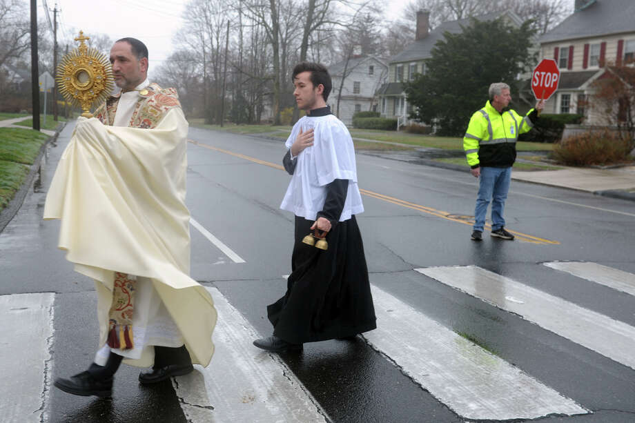 Father Peter Cipriani from Our Lady of Assumption Church leads a Sunday eucharistic procession around the Stratfield neighborhood of Fairfield, Conn. March 29, 2020. Cipriani has been leading the weekly processions following closed masses that are still held at the church. The masses can be viewed by a live stream on the church's website, as well as social media. The church is currently closed to the public due to coronavirus precautions. Photo: Ned Gerard, Hearst Connecticut Media / Connecticut Post