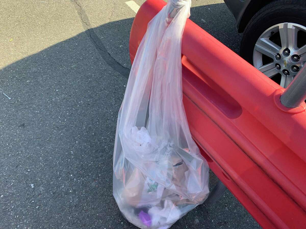 Araceli Bermudez of Bridgeport took off her gloves in the parking lot of Shelton's Shop Rite and dropped them in this bag attached to a shopping cart retrieval center.
