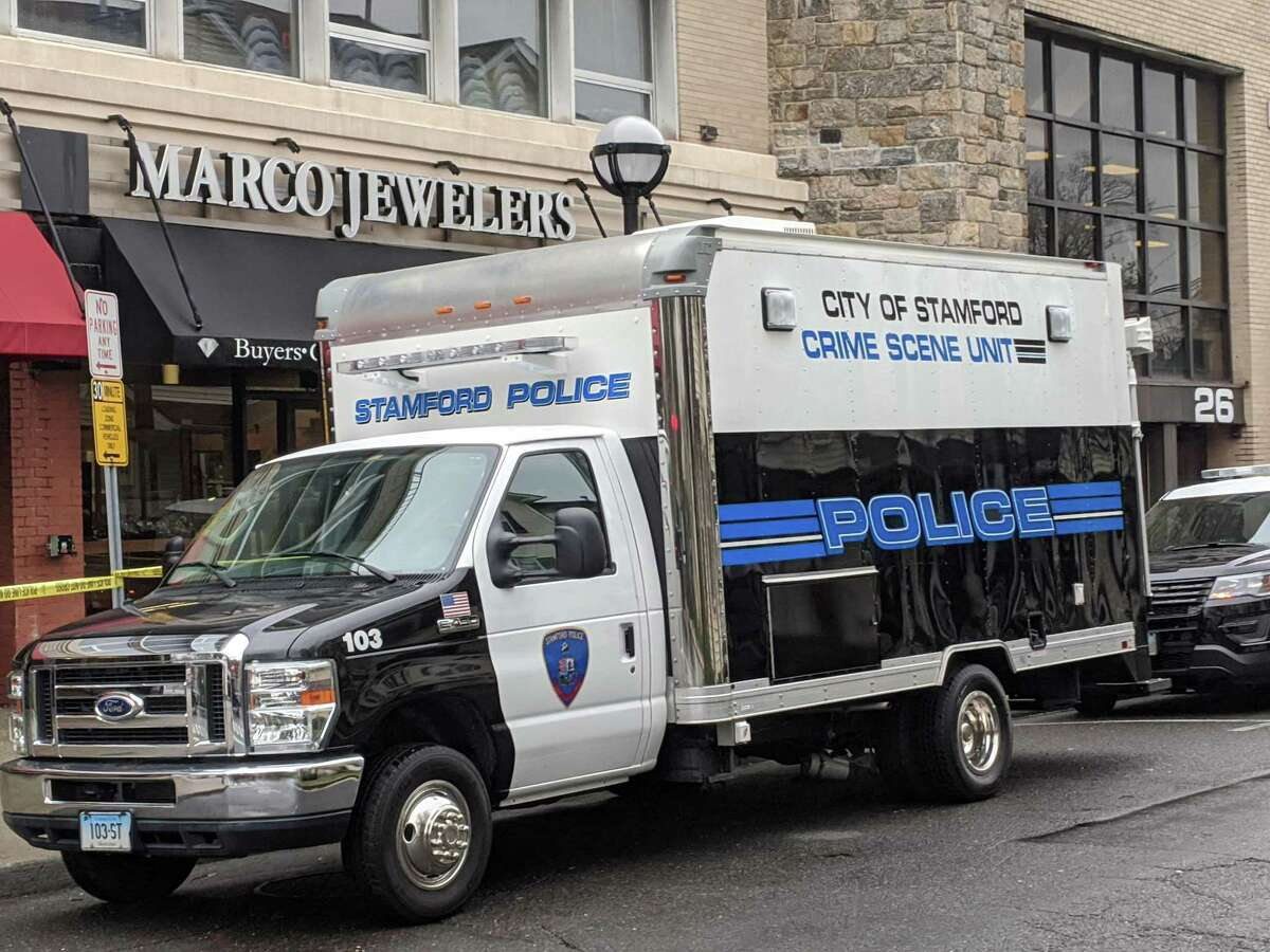 Stamford police vehicles are parked outside Marco Jewelers on 6th Street Sunday afternoon. Police say the owner of the store was shot and killed during an afternoon robbery on Saturday.