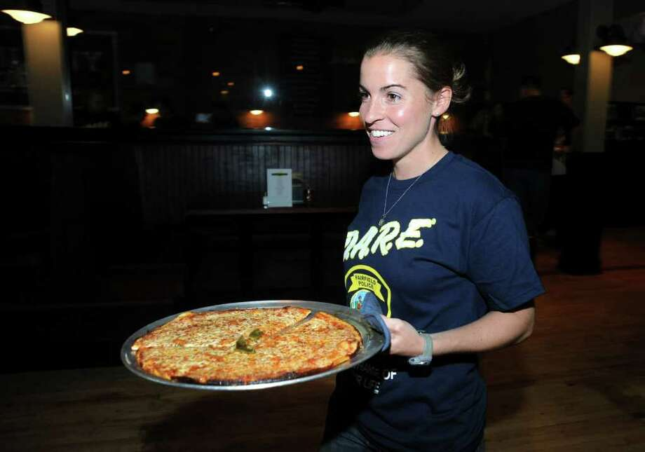 Fairfield Police Officer Lisa Burbige serves up a cheese pie August 18, 2010 at Colony Grill in Fairfield.  Police officers worked as waitstaff to collect tips to benefit the American Cancer Society's Kick-It Motorcycle Ride. Photo: Autumn Driscoll / Connecticut Post