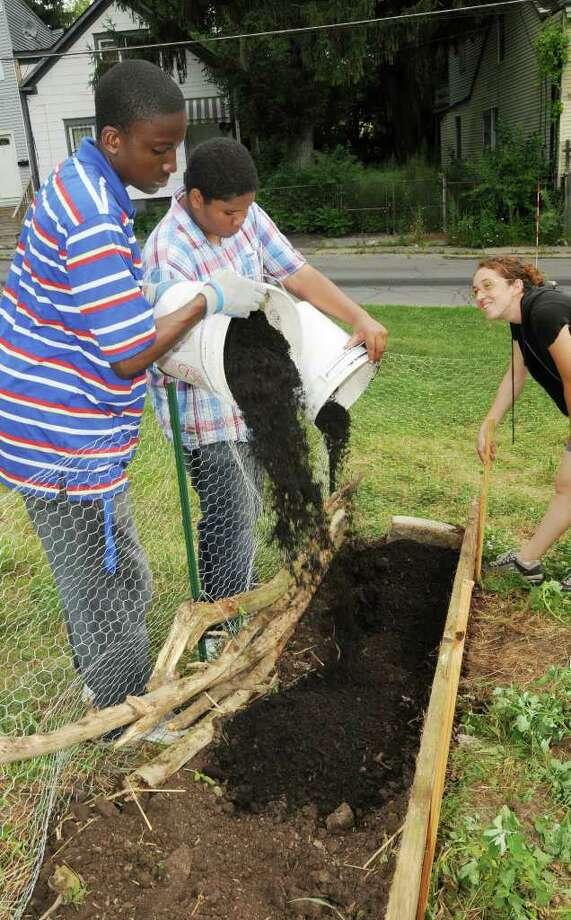 Akil Hamilton, 17, Dedree Clarke, 15, and Rana Morris install a garden box intended to house snap peas. (Luanne M. Ferris / Times Union) Photo: Luanne M. Ferris