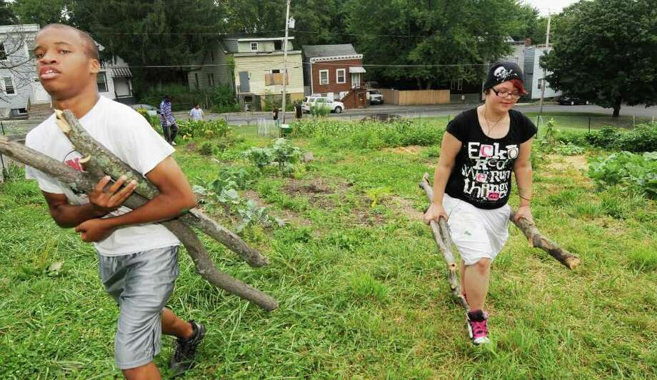 Anthony Ballou, 15, and Jessica Quinlan gather tree limbs for the fence. (Luanne M. Ferris / Times Union) Photo: Luanne M. Ferris