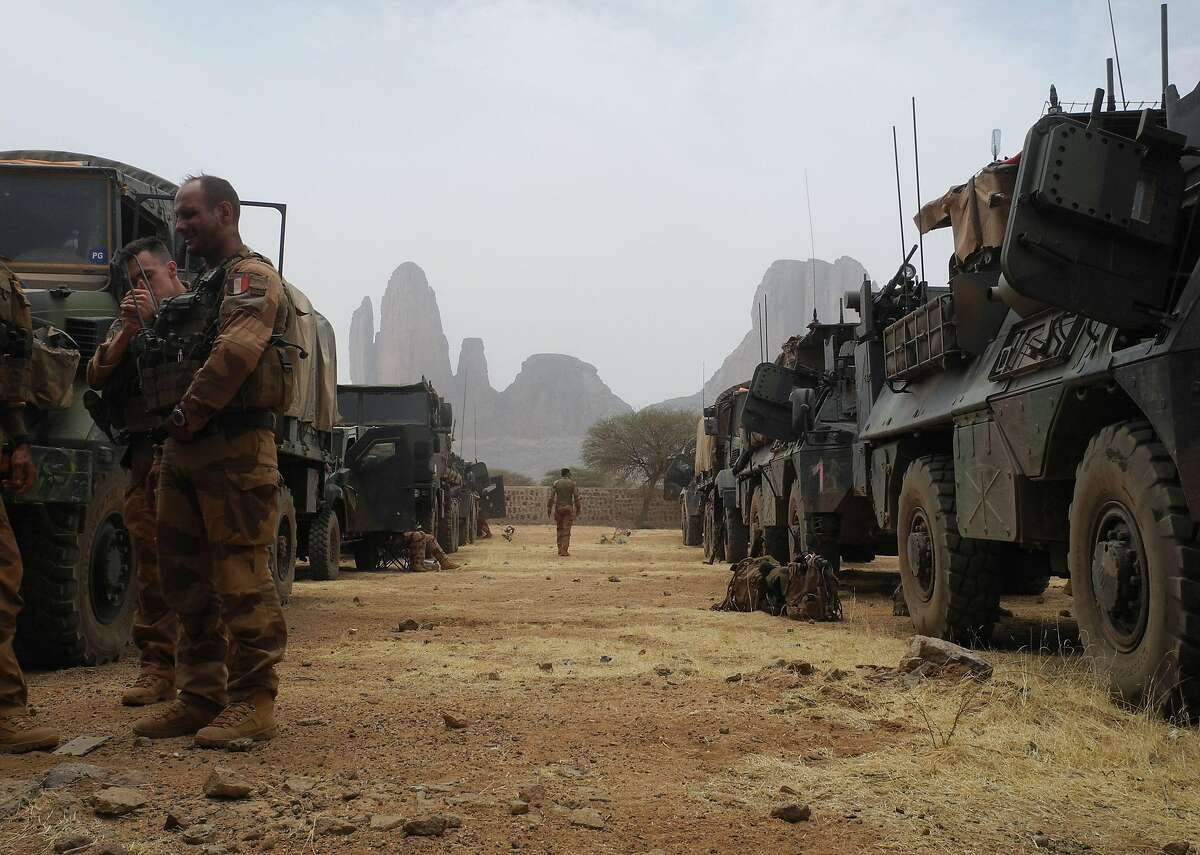(FILES) In this file photo taken on March 27, 2019 French soldiers stand by a convoy of armoured vehicles with the Mount Hombori in the background during the start of the French Barkhane Force operation in Mali's Gourma region. - The Malian, Nigerian armies and the French Barkhane force carried out in March an operation of an