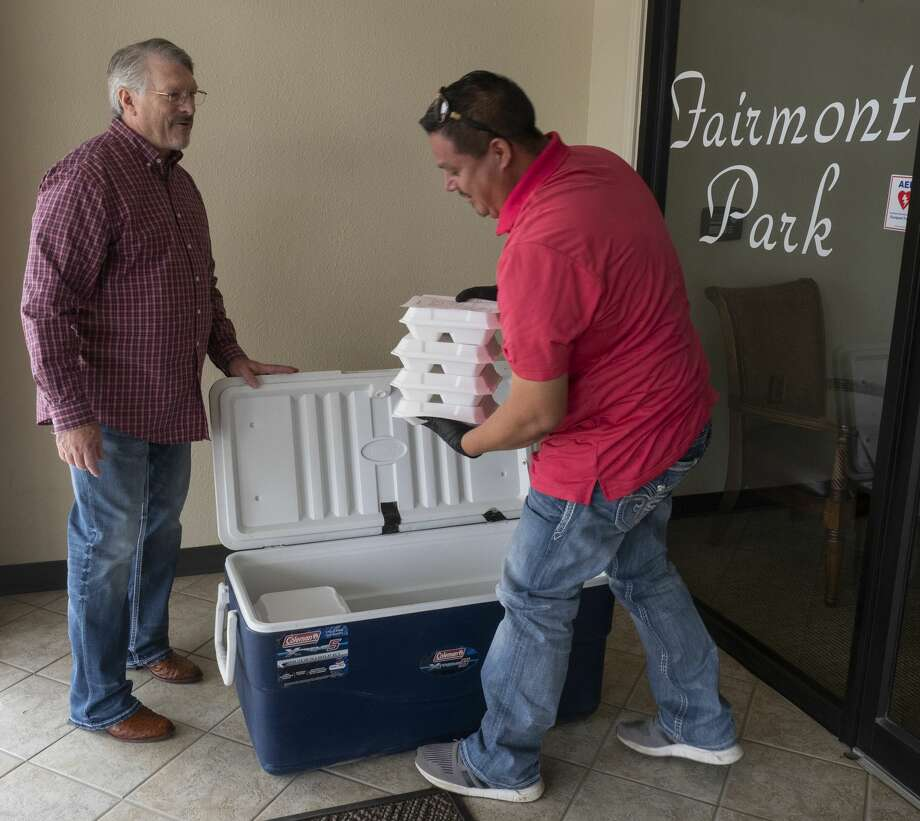 Pastor Tim Baugh holds open the cooler as Gus Pizarro gets meals to deliver 03/29/2020 afternoon. Members of Fairmont Park Church of Christ cooked deep fried turkey, stuffing, green bean casserole and mashed potatoes for their congregation and the community to pickup Sunday at the church. Tim Fischer/Reporter-Telegram Photo: Tim Fischer/Midland Reporter-Telegram