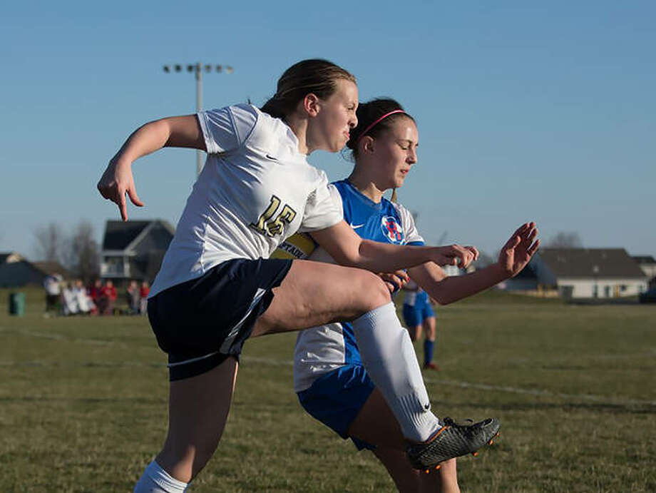 Father McGivney's Macy Hoppes, left, chases down the ball during a game last season. Photo: For The Intelligencer
