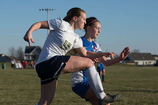 Father McGivney's Macy Hoppes, left, chases down the ball during a game last season.