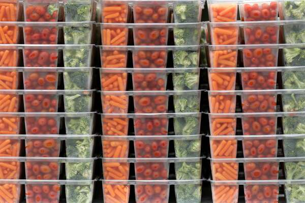 Stacked vegetables are seen as volunteers and staffs with The Woodlands Family YMCA and the Montgomery County Food Bank help give out food to families, Saturday, March 28, 2020, in The Woodlands. Two hundred families received 40-pounds of food in the organizations?• mobile market.