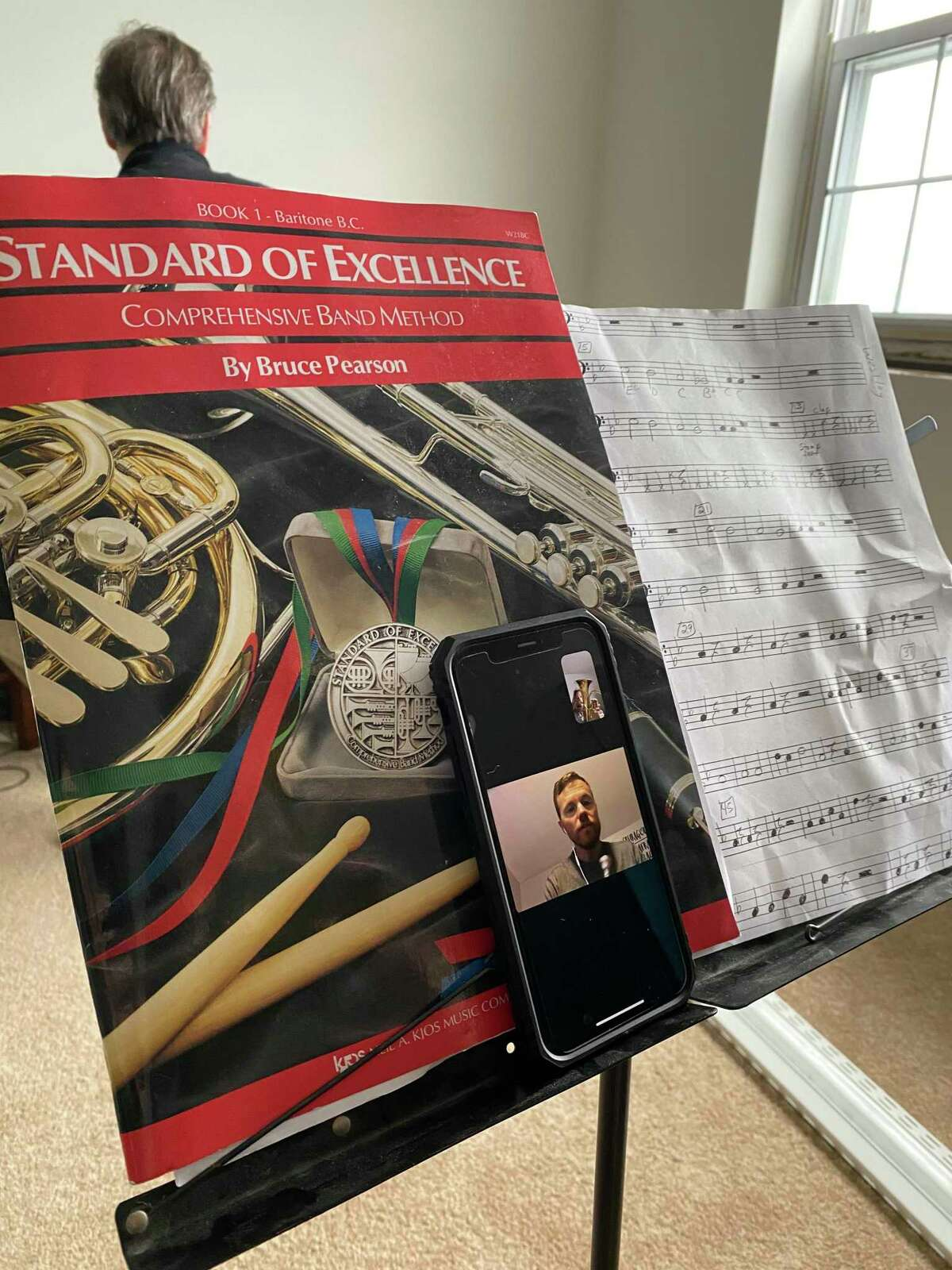Westley Soreff, a fifth-grade student at Jefferson Elementary School, gets his music stand arranged - book, sheet music, and his teacher on FaceTime.