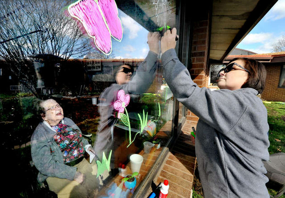 Delores, a 102-year-old resident of Eden Village Retirement Community in Glen Carbon, left, watches as Dawn Biersborn of Collinsville colors in a butterfly and flowers on her window Sunday. Because of the COVID-19 pandemic, retirement home residents cannot receive visitors, so a group of volunteers decorated their windows, held up signs, and brought a dressed-up dog and horse for the residents to look at through their windows.