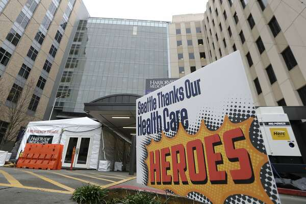 """A sign posted in front of the emergency entrance of Harborview Medical Center gives thanks to health care workers during the coronavirus outbreak Saturday, March 28, 2020, in Seattle. Harborview and University of Washington Medicine are preparing a """"surge plan"""" that will enable its hospitals to better respond to the coronavirus outbreak. Under the plan, ambulatory patients with respiratory illness symptoms will be separated from other patients when they arrive at hospitals' emergency departments and be directed to a new treatment area in a tent outside of the emergency department. (AP Photo/Elaine Thompson)"""