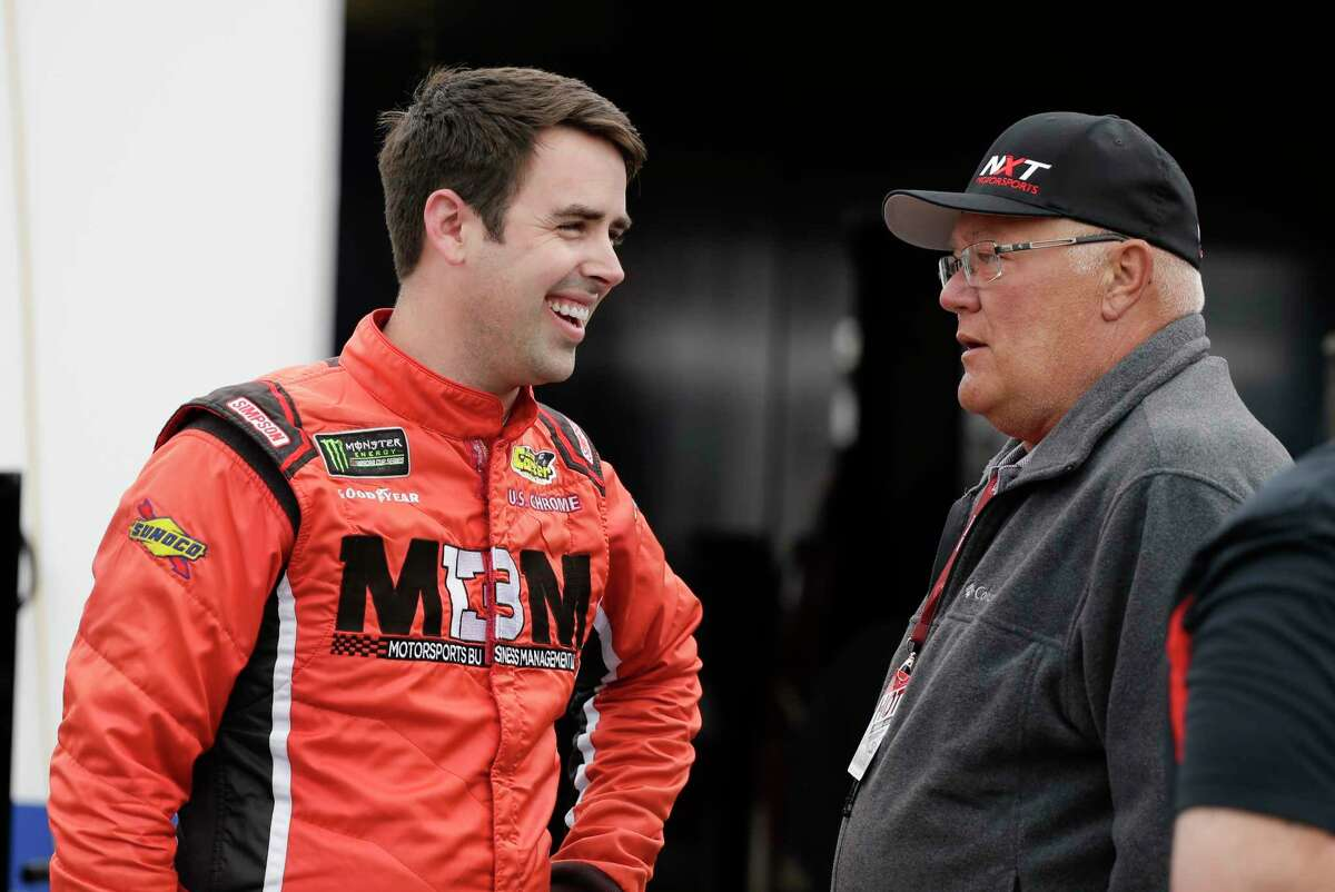 Timmy Hill, left, talks with members of his team in the garage area during NASCAR auto race practice at Daytona International Speedway, Friday, Feb. 14, 2020, in Daytona Beach, Fla. (AP Photo/Terry Renna)