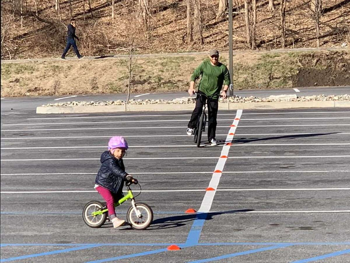 Signs of normalcy and spring: Andy Choens took advantage of the empty parking at Guilderland Public Library recently to teach his four-year-old daughter, Leila, how to ride a bicycle.