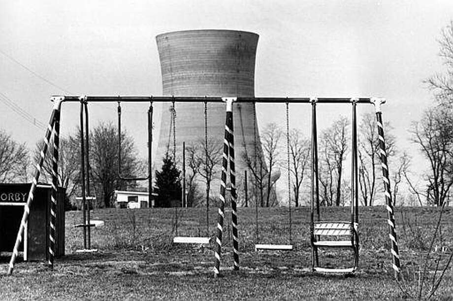 A cooling tower of the Three Mile Island nuclear power plant near Harrisburg, Pa., looms behind an abandoned playground, March 30, 1979. (AP Photo/Barry Thumma)