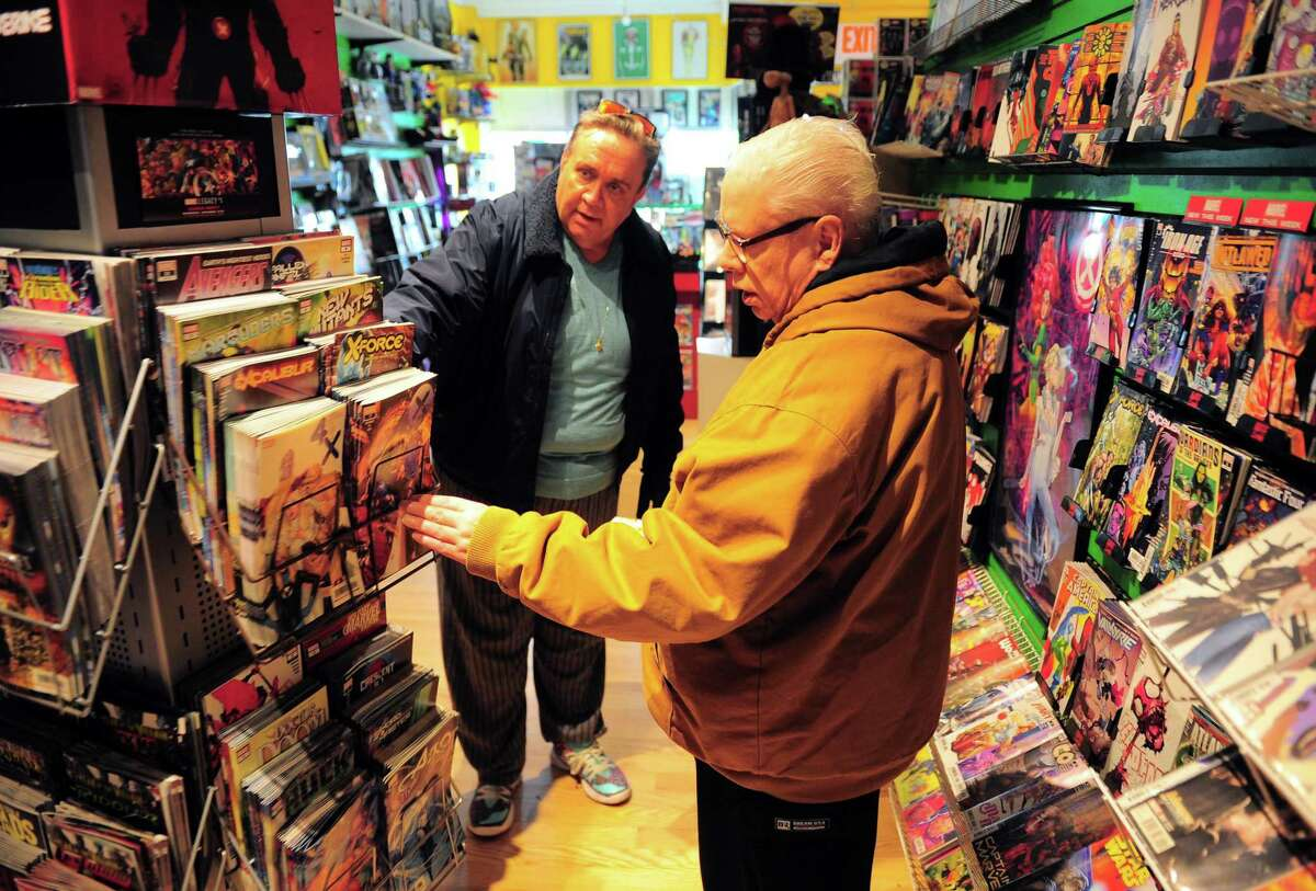 Kevin Kane, in back, helps his brother Richard shop at Rogue Comics in the Black Rock section of Bridgeport, Conn., on Wednesday Mar. 25, 2020. Owner Michael Fuller is trying to get a waiver from the state to remain open. As part of the social distancing guidelines, the Kane brothers came to visit by appointment only.