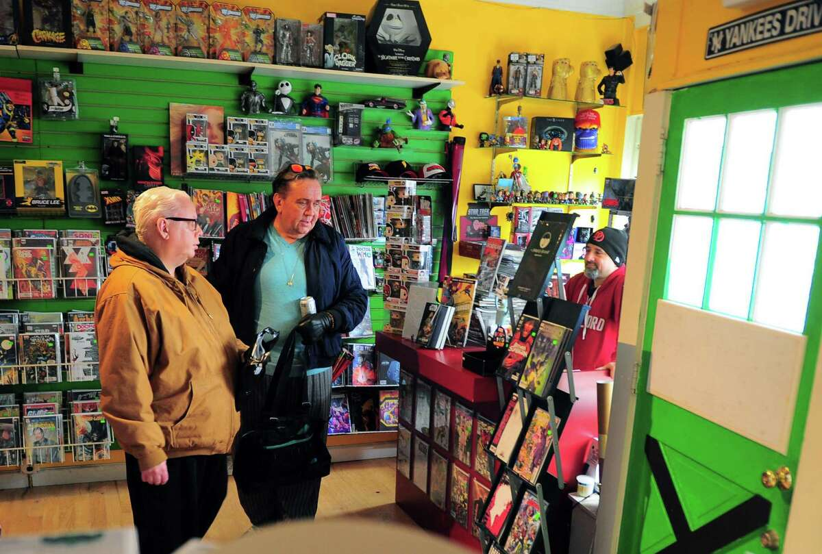 Rogue Comics owner Michael Fuller, at right, waits on brothers Richard and Kevin Kane, center, at the store in the Black Rock section of Bridgeport, Conn., on Wednesday Mar. 25, 2020. Owner Michael Fuller is trying to get a waiver from the state to remain open. For now he is letting customers come by appointment only.
