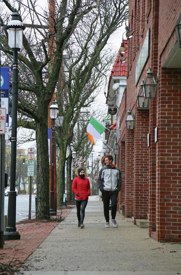 Jim Romanelli of Fairfield and Maria Ammosova of Union City, N.J., enjoy a quiet walk on the Post Road on Sunday, March 29, 2020, in Fairfield, Conn. Photo: Jarret Liotta / Jarret Liotta / ©Jarret Liotta 2020