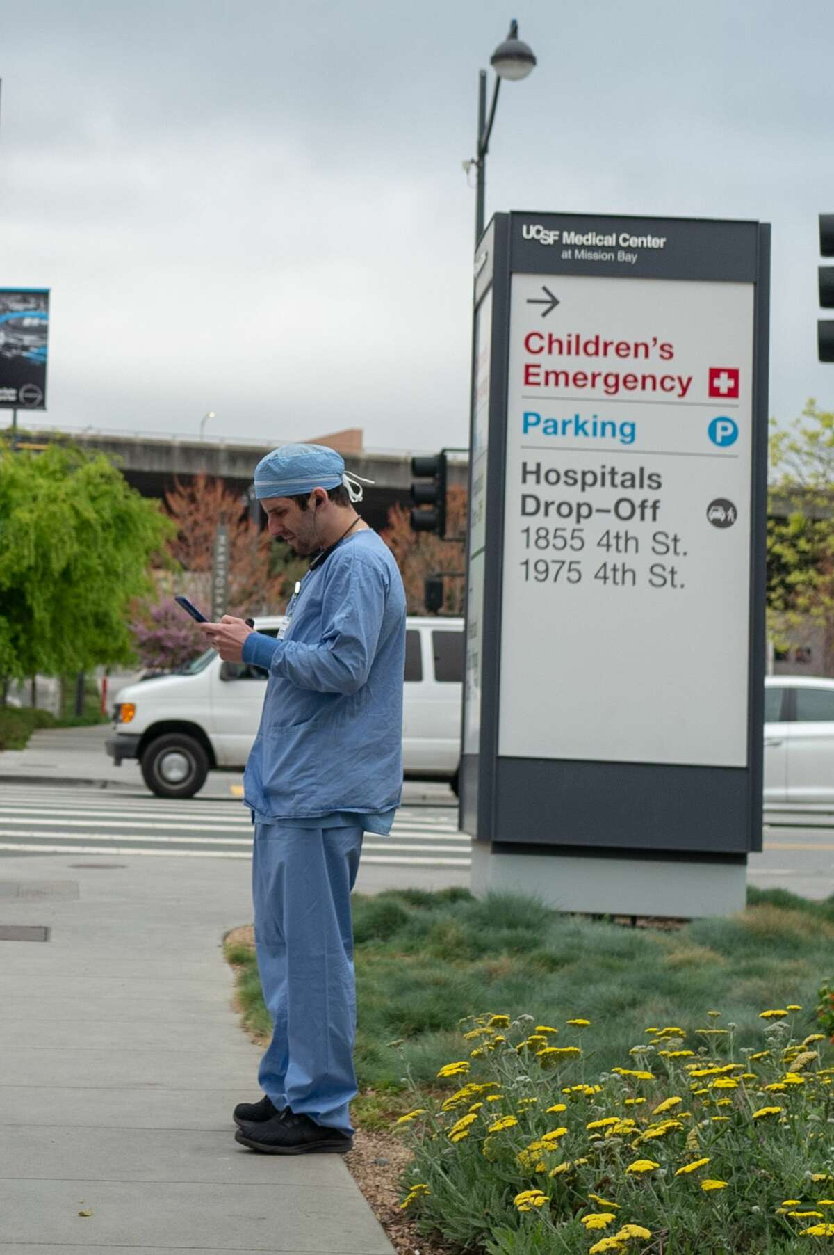 A medical provider in scrubs stands near a sign outside the University of California San Francisco (UCSF) medical center in Mission Bay during an outbreak of the COVID-19 coronavirus in San Francisco, California, March 23, 2020.
