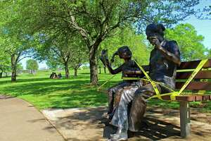 A statue at Sugar Land's Oyster Creek Park was wrapped with tape Friday, March 27. In the background, couples sat on the lawn to enjoy picnics, avoid the hard surfaces of picnic tables and benches where medical experts say the COVID-19 virus could live for hours to days.