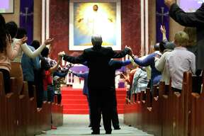 Worshippers hold hands across the aisles during Sunday Mass at Catholic Charismatic Center 1949 Cullen, in Houston,Sunday, March 15, 2020. The church normally has as many as 1,200 parishioners on Sundays, however, many people opted to watch live online, as fears of being in large groups may have kept people home.