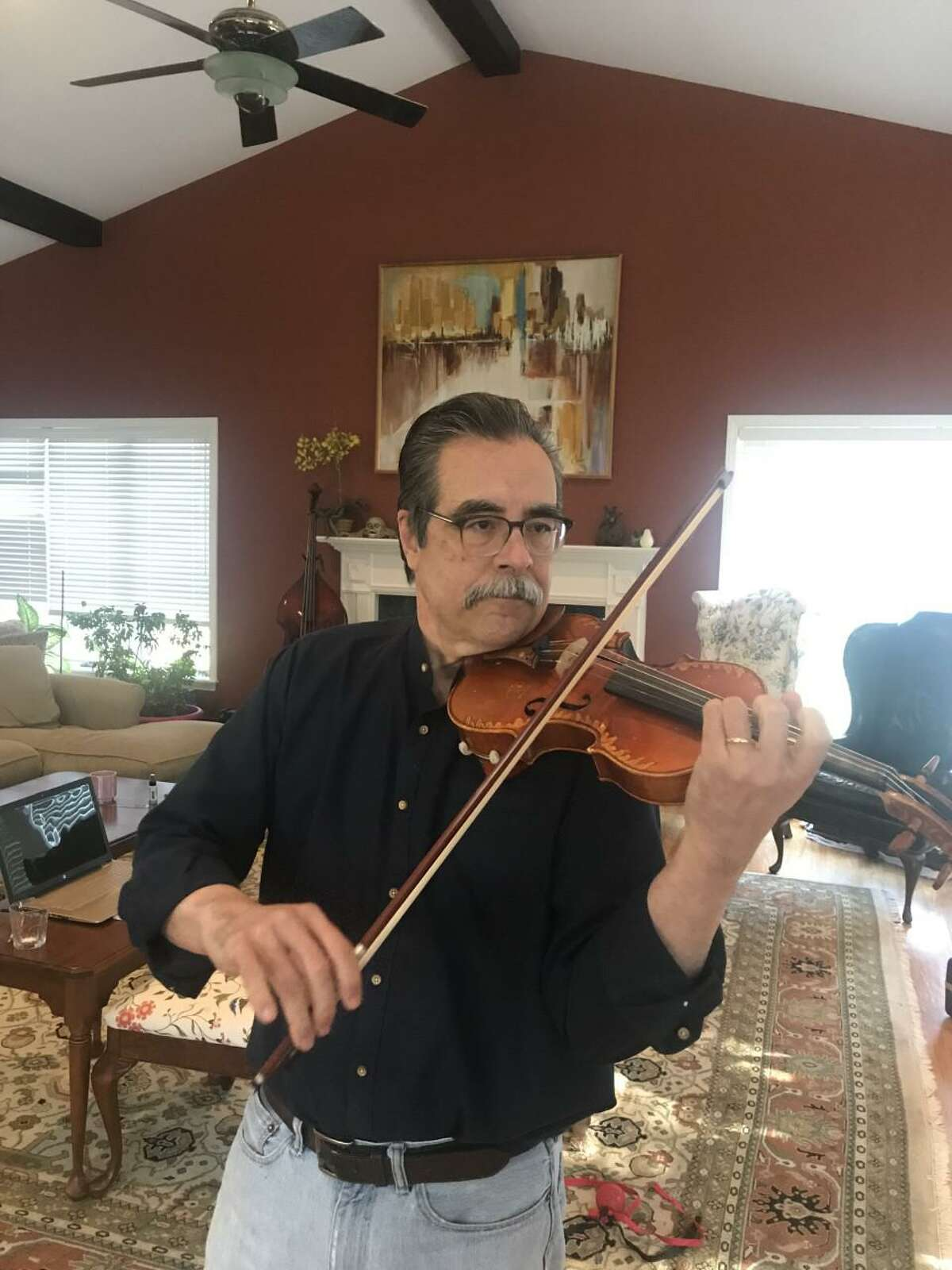 Mac Johnston plays the violin in his living room in Wilton.