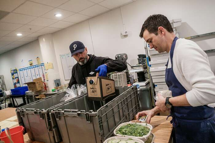 Daily Driver owner David Kreitz, left, and Marty Siggins pack up breakfast to be delivered to Hospital workers at UCSF as a part of Feed the Line in San Francisco, Calif. on Saturday March 28, 2020.