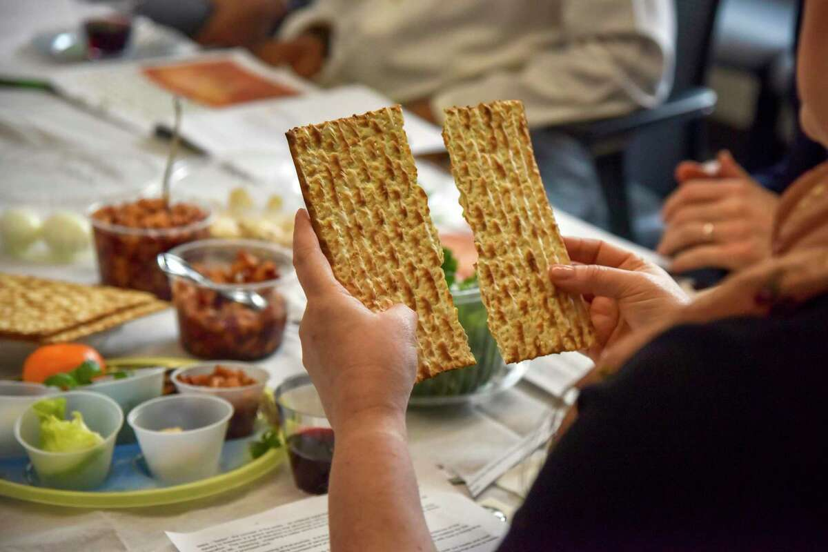 Rabbi Janet Ozur Bass breaks a piece of unleavened bread at an Interfaith Passover seder hosted by Montgomery County council member Sidney Katz at the Montgomery County Council Office Building on Wednesday, April 24, 2019, in Rockville, MD.