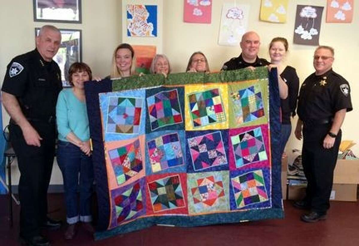 Quilt hand-stitched by men and women at the Columbia County Jail, held by Sarris (in blue) and her community partners. The quilt was given to Columbia Opportunities and donated to a needy family.