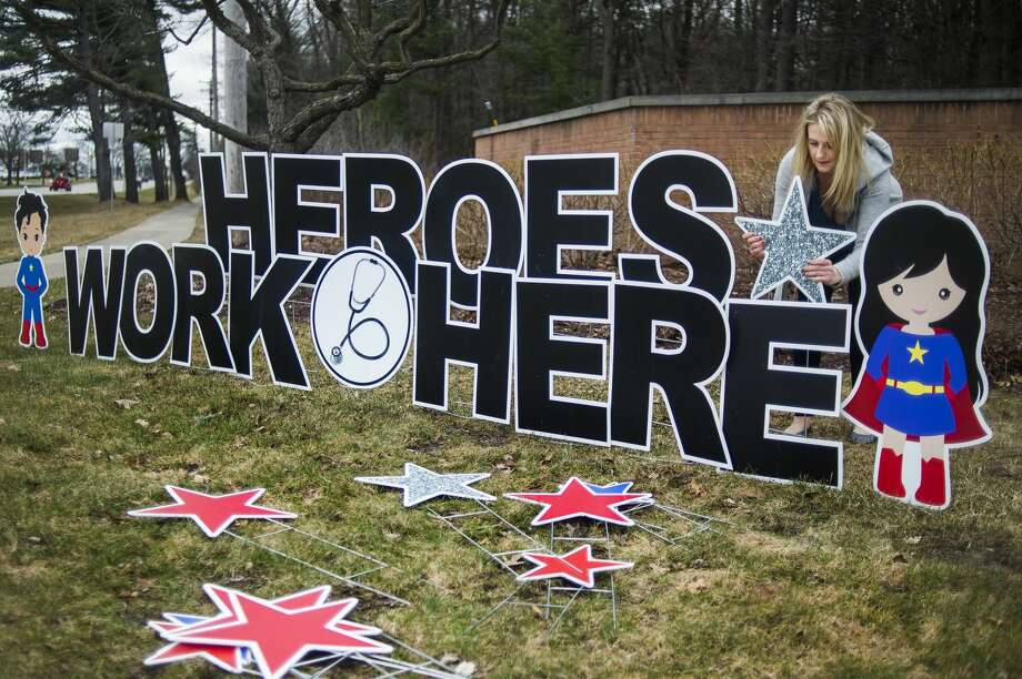 "Morgan Jackson, owner of Sign Gypsies Mid Michigan, installs a sign honoring hospital workers at the Saginaw Road entrance for MidMichigan Medical Center - Midland Monday, March 30, 2020. Jackson donated the sign, which reads ""Heroes work here,"" to thank hospital staff for their hard work and long hours during the coronavirus pandemic. (Katy Kildee/kkildee@mdn.net) Photo: (Katy Kildee/kkildee@mdn.net)"